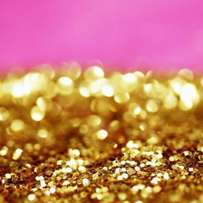gold glittering particles against pink for Glitz, Glamour and a bit of Sparkle